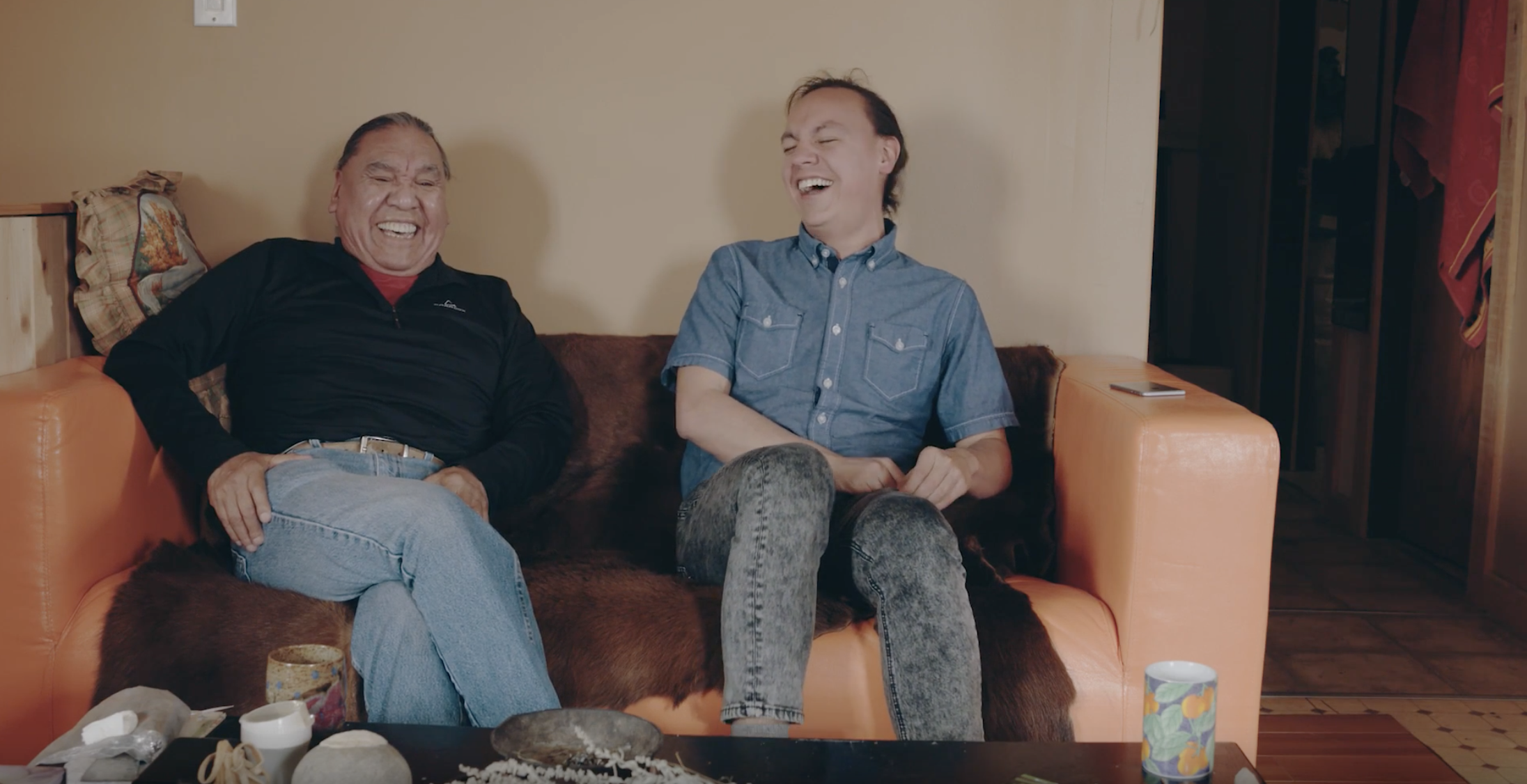 Picture of Max with his dad sitting on a couch laughing.