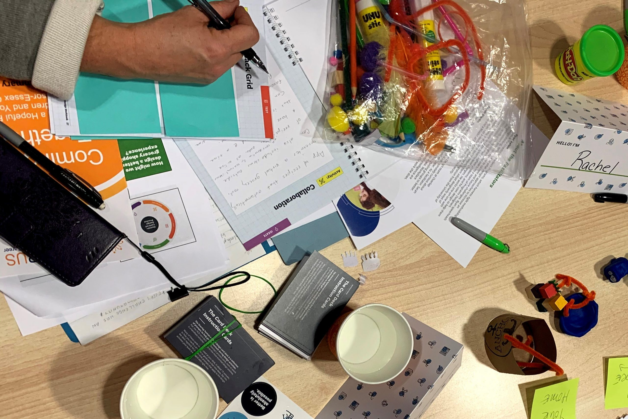 A table filled with training materials and a workbook where someone is taking notes.